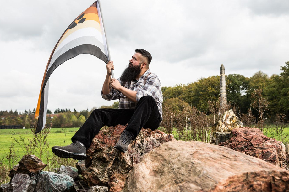 Sitting on top of an enormous piece of petrified wood in Baarn, holding our BEAR community's pride flag, with the 'Naald van Waterloo' monument visible in the background. | Beards  Porn XXX | Hot XXX Gays